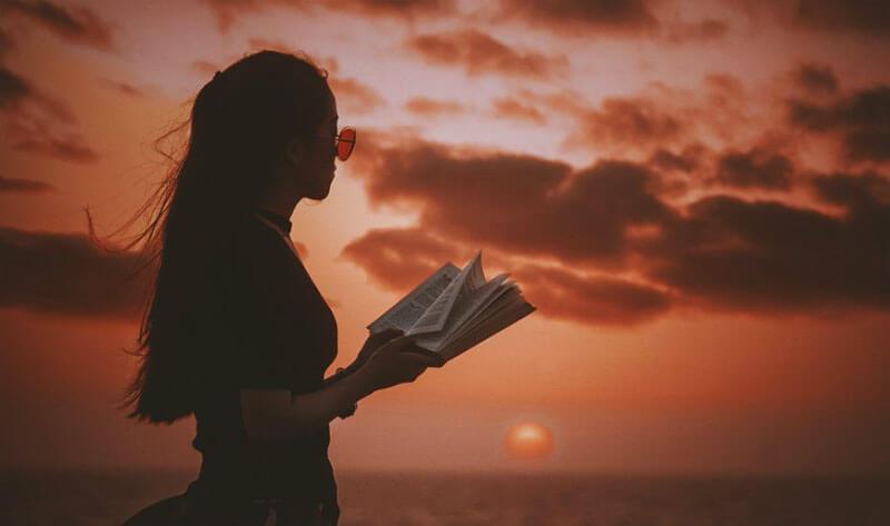 Hình ảnh bạn nữ đọc sách dưới hoàng hôn buồn